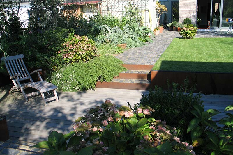 Garten mit Holzterrasse und Natursteinweg